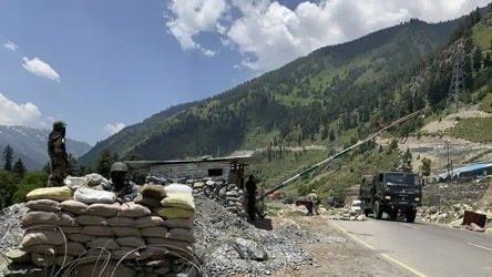 Indian paramilitary soldiers keep guard as Indian army convoy moves on the Srinagar Ladakh highway at Gagangeer northeast of Srinagar